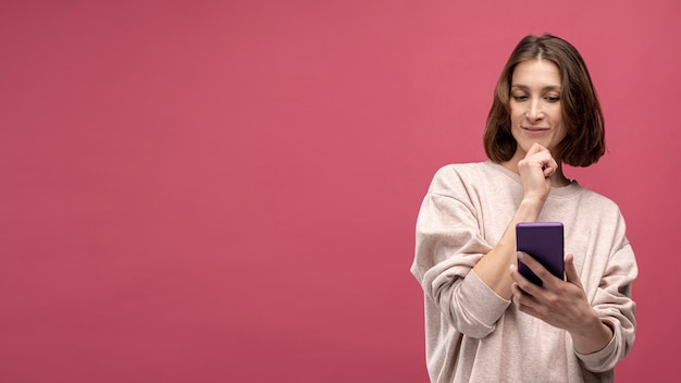 Vooraanzicht van vrouw die terwijl het houden van smartphone denken