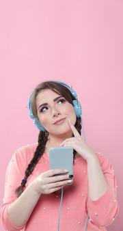 Vooraanzicht van vrouw die terwijl het houden van telefoon en vinger stelt alsof zij denkt