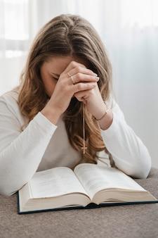 Vooraanzicht van vrouw die thuis bidt