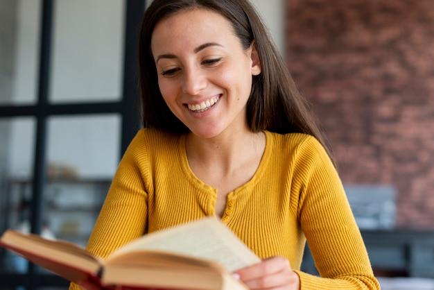 Vooraanzicht van vrouw die van boek geniet