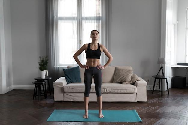 Vooraanzicht van vrouw die voor oefeningen thuis voorbereidingen treft