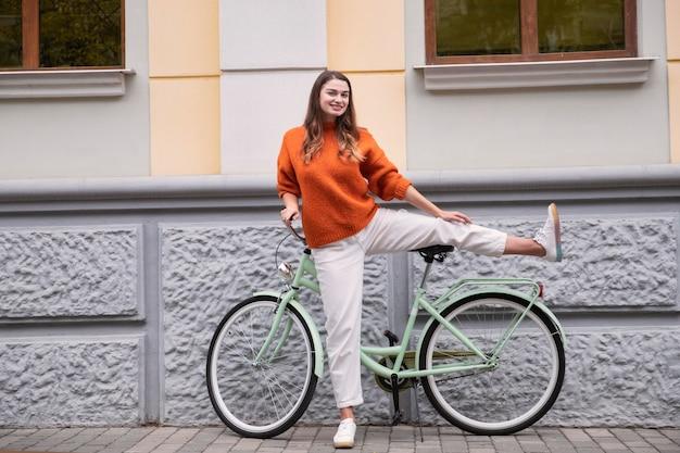 Vooraanzicht van vrouw dwaas poseren met haar fiets buitenshuis