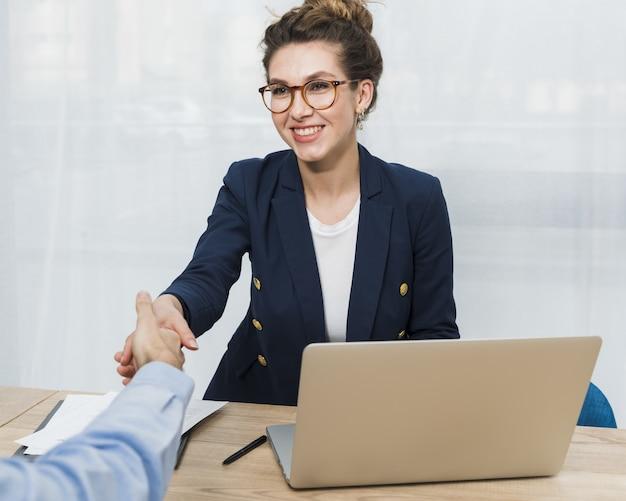Vooraanzicht van vrouw hand schudden met man komt voor sollicitatiegesprek