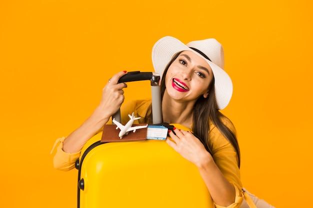 Vooraanzicht van vrouw het stellen met bagage en reisbenodigdheden