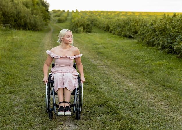 Vooraanzicht van vrouw in rolstoel buitenshuis