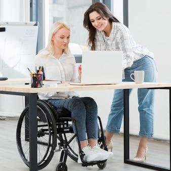 Vooraanzicht van vrouw in rolstoel die bij bureau werkt