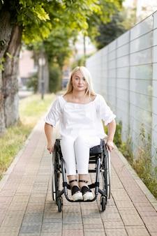 Vooraanzicht van vrouw in rolstoel in de stad