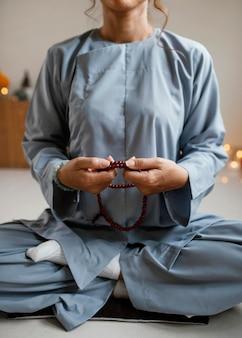 Vooraanzicht van vrouw mediteren met kralen