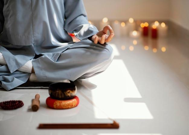 Vooraanzicht van vrouw mediteren met wierook en kaarsen