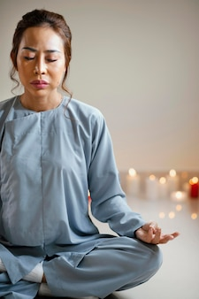 Vooraanzicht van vrouw mediteren naast kaarsen met kopie ruimte
