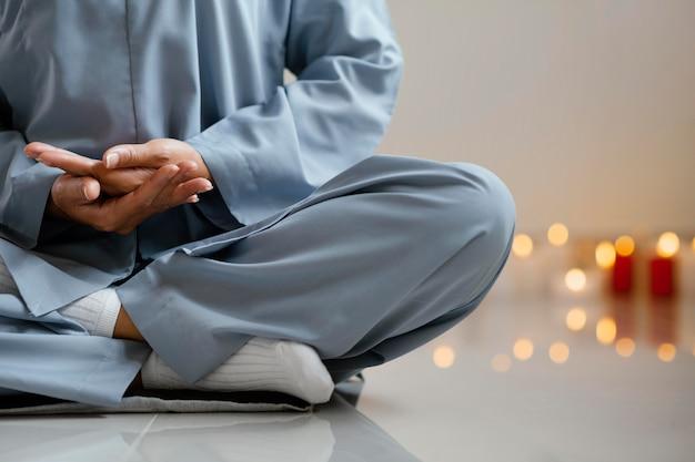 Vooraanzicht van vrouw mediteren naast kaarsen