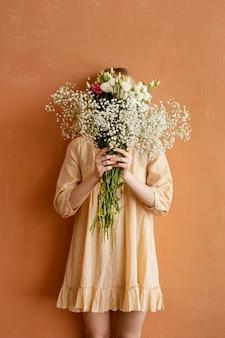 Vooraanzicht van vrouw met boeket van prachtige lentebloemen