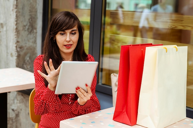 Vooraanzicht van vrouw met boodschappentassen bestellen van artikelen te koop met behulp van tablet