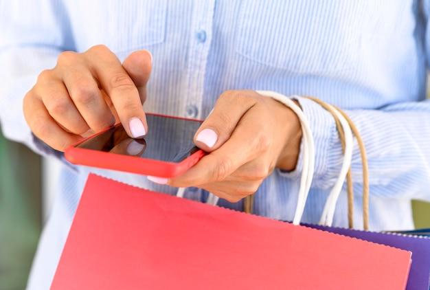 Vooraanzicht van vrouw met boodschappentassen en smartphone voor cyber maandag