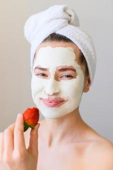 Vooraanzicht van vrouw met de holdingsaardbei van het gezichtsmasker