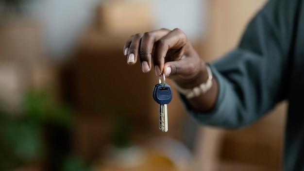Vooraanzicht van vrouw met de sleutels van haar nieuwe huis