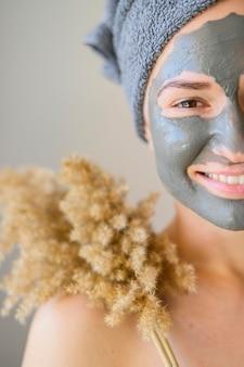 Vooraanzicht van vrouw met gezichtsmasker het stellen met bloem