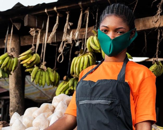 Vooraanzicht van vrouw met gezichtsmasker in markt