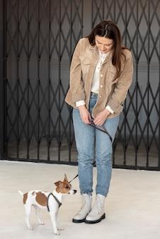 Vooraanzicht van vrouw met haar hond die een leiband draagt