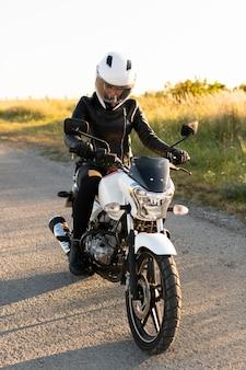 Vooraanzicht van vrouw met helm die haar motorfiets berijdt