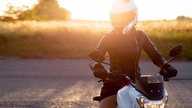 Vooraanzicht van vrouw met helm die haar motorfiets in de zonsondergang berijdt