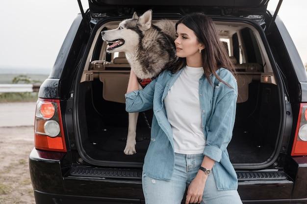 Vooraanzicht van vrouw met husky die met de auto reist