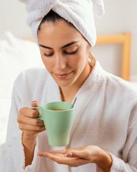 Vooraanzicht van vrouw met koffie thuis na bad
