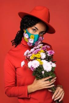 Vooraanzicht van vrouw met masker en boeket bloemen