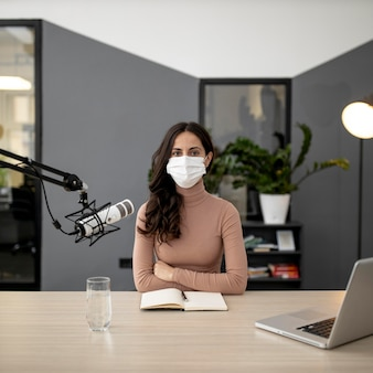 Vooraanzicht van vrouw met medisch masker dat op radio uitzendt