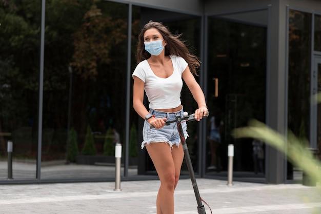 Vooraanzicht van vrouw met medisch masker die een elektrische autoped berijdt