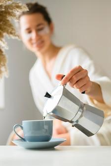Vooraanzicht van vrouw met ooglapjes die koffie gieten