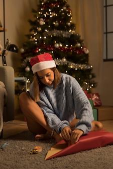 Vooraanzicht van vrouw met santahoed die giften verpakken