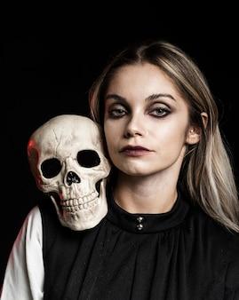 Vooraanzicht van vrouw met schedel op schouder