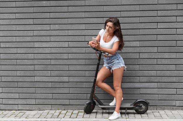 Vooraanzicht van vrouw met smartphone zittend op scooter
