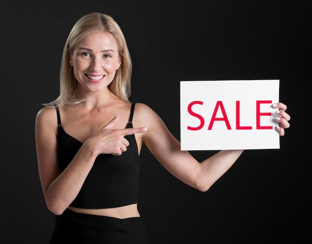 Vooraanzicht van vrouw met verkoopaanplakbiljet