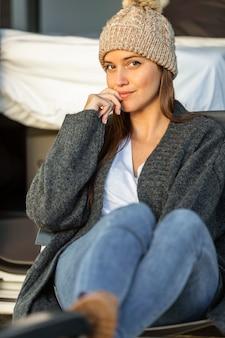Vooraanzicht van vrouw ontspannen naast auto tijdens een road trip