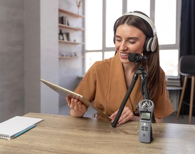Vooraanzicht van vrouw podcasting met microfoon en tablet