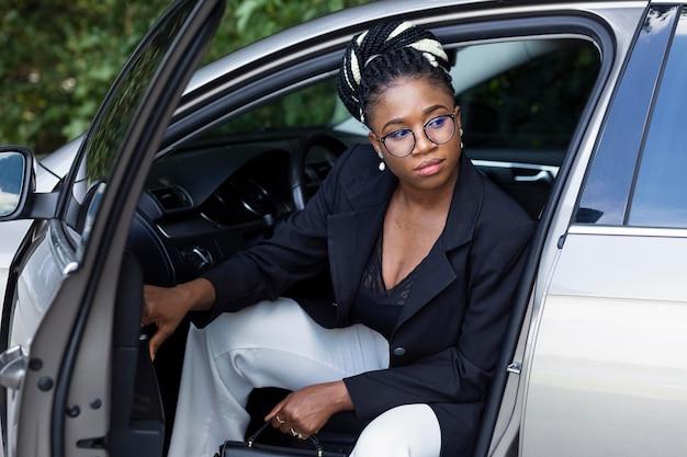 Vooraanzicht van vrouw poseren vanaf de voorstoel van haar auto