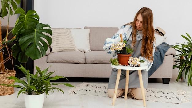 Vooraanzicht van vrouw thuis aanplant