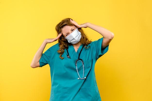 Vooraanzicht van vrouwelijke arts beklemtoond in masker op gele muur