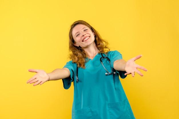 Vooraanzicht van vrouwelijke arts die enkel op gele muur glimlacht