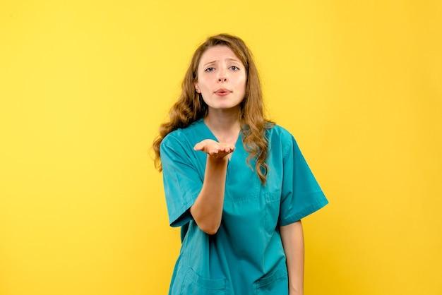 Vooraanzicht van vrouwelijke arts die liefde op gele muur verzendt