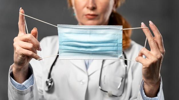 Vooraanzicht van vrouwelijke arts die medisch masker houdt