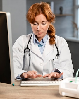 Vooraanzicht van vrouwelijke arts die op computer bij bureau typen