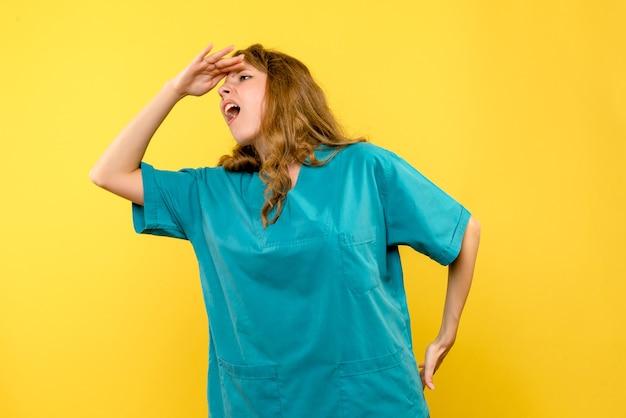Vooraanzicht van vrouwelijke arts die op gele muur kijkt