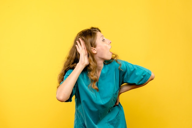 Vooraanzicht van vrouwelijke arts die op gele muur probeert te luisteren