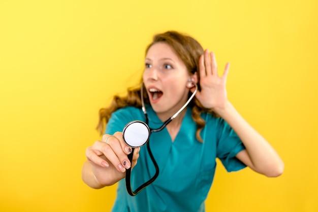 Vooraanzicht van vrouwelijke arts die stethoscoop op gele muur met behulp van