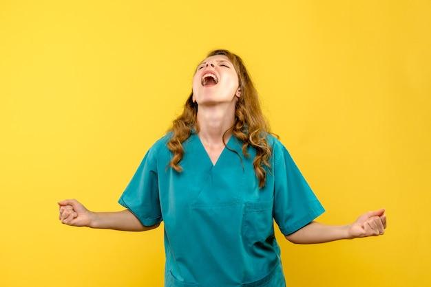 Vooraanzicht van vrouwelijke arts die zich op gele muur verheugt