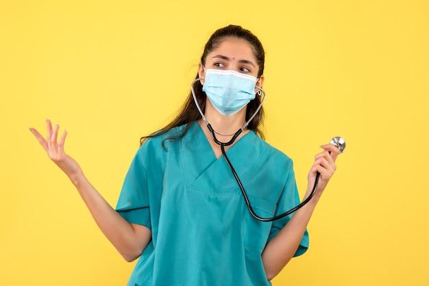Vooraanzicht van vrouwelijke arts in eenvormige holdingsstethoscoop die zich op gele muur bevindt