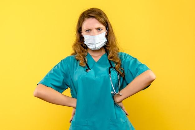 Vooraanzicht van vrouwelijke arts in masker op gele muur